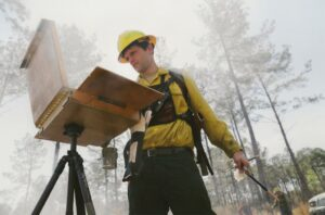 Philip Juras painting a prescribed fire.